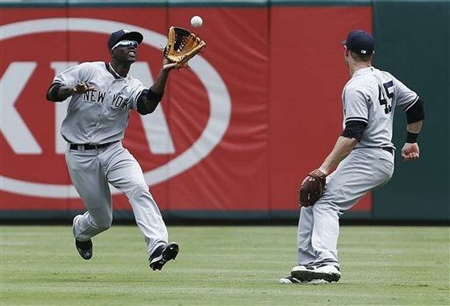 New York Yankees second baseman David Adams (45) looks on as center fielder Melky Mesa, left, catches a fly ball hit by Texas Rangers' Leonys Martin in the fifth inning of a baseball game in Arlington, Texas, Thursday, July 25, 2013. (AP Photo/Brandon Wade) Photo: AP / FR168019 AP