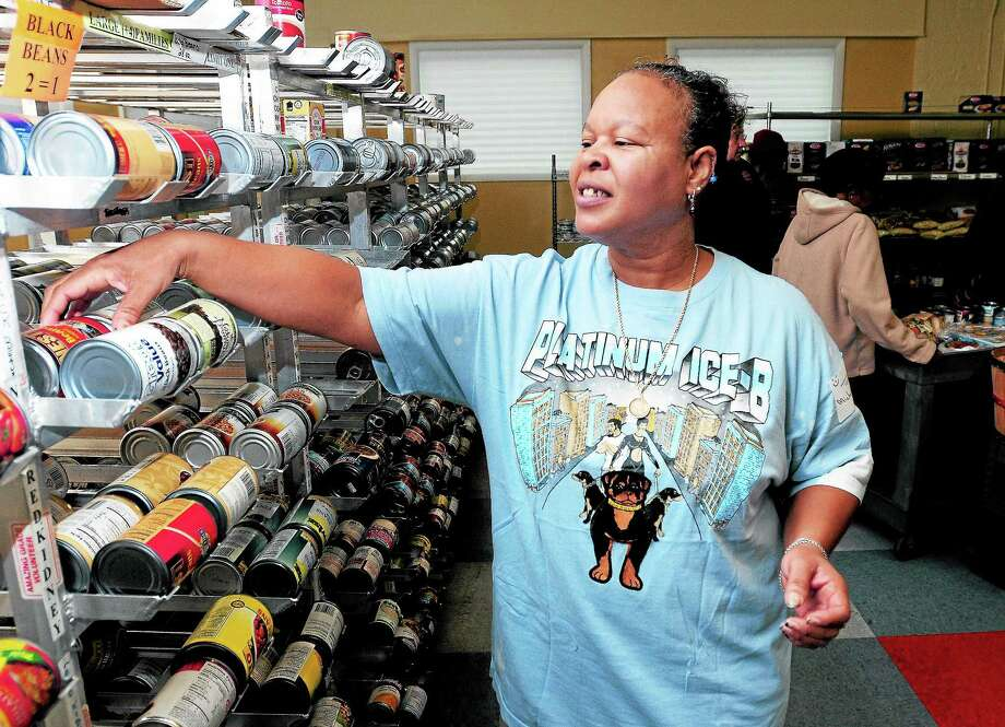 Michele Foye of Middletown gathers food at the Amazing Grace Food Pantry in Middletown. Photo: Arnold Gold — New Haven Register