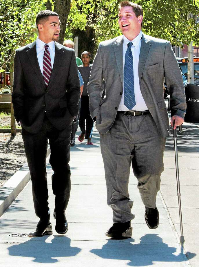 (Melanie Stengel — New Haven Register )  East Haven Police Officer, David Cari (R), and a member of his defense team  leave U.S. District Court in Hartford for a lunch break on Monday. Photo: Journal Register Co.