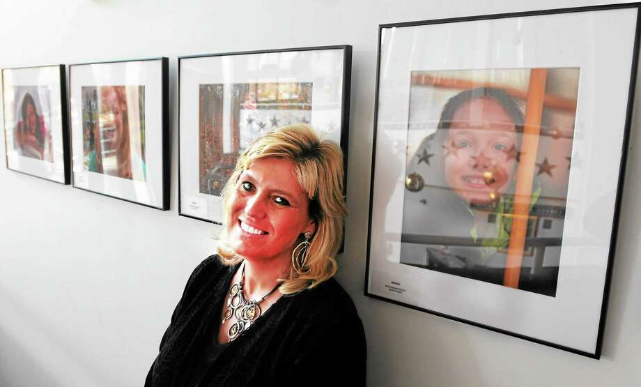 Jacqueline Ford of the Connecticut Office of Foster Care and Adoption Services  with some portraits of children on exhibit at the Shubert Theater in New Haven. Photo: Peter Hvizdak — New Haven Register       / ©Peter Hvizdak /  New Haven Register
