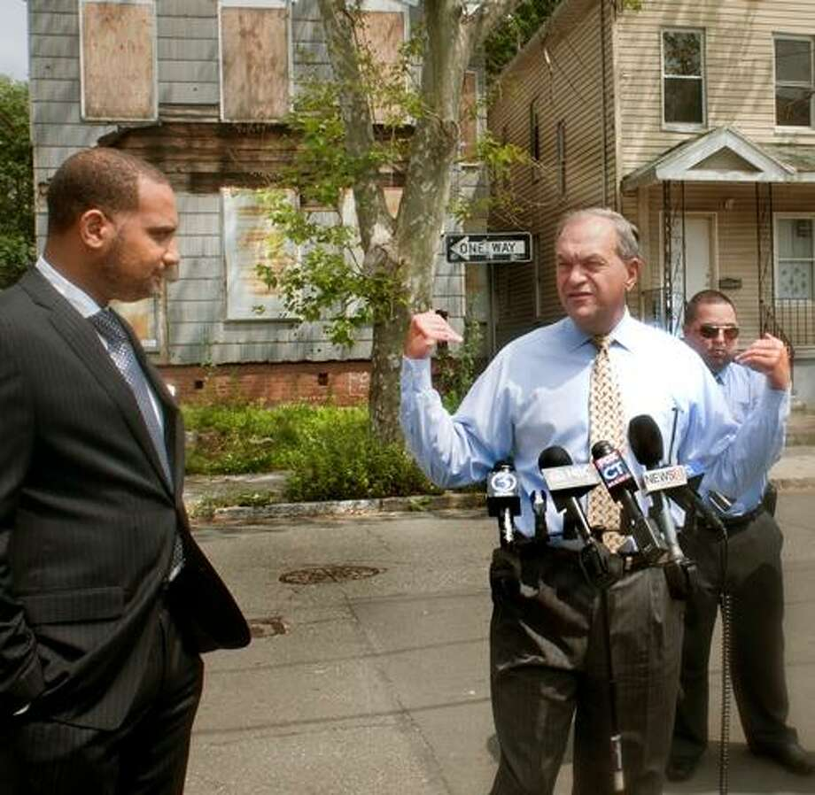 In this file photo: l to r, Erik Johnson, Executive director of Livable Cities Initiative; Mayor John DeStefano, and former alderman Joey Rodriguez  in front of 129 Clay Street,. The property has been aquired by the city of New Haven. The house will be rehabbed.  Melanie Stengel/Register