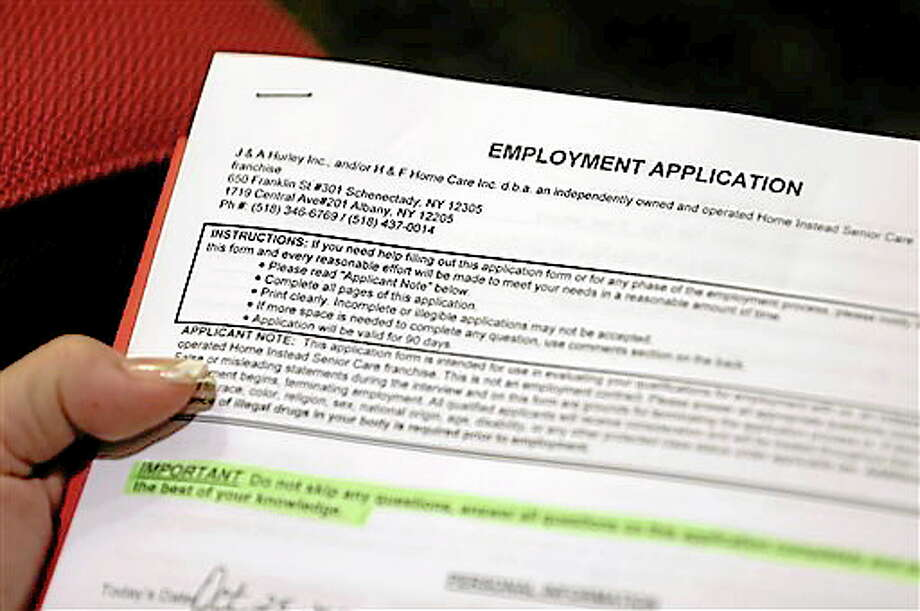 In this Thursday, Oct. 25, 2012, photo,  Carmen Nazario of Albany, N.Y., fills out an employment  application during a job fair at the Marriott Hotel in Colonie, N.Y. The number of Americans seeking unemployment benefits fell 23,000 to a seasonally adjusted 393,000 for the last full week of November 2012. It was the second straight drop after Superstorm Sandy had driven applications much higher earlier in November (AP Photo/Mike Groll) Photo: ASSOCIATED PRESS / A2012