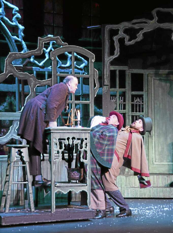 """Scrooge scares the life out of a couple of charity workers in """"A Christmas Carol,"""" coming Friday to the Shubert. Photo: Contributed Photo"""