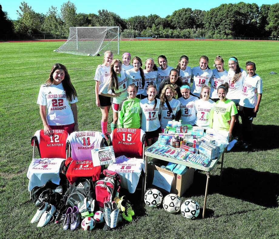 Paige Dostie, left, and the rest of the Sacred Heart Academy soccer team helped organize an effort to send soccer equipment and medical supplies to Haiti. Photo: Arnold Gold — Register
