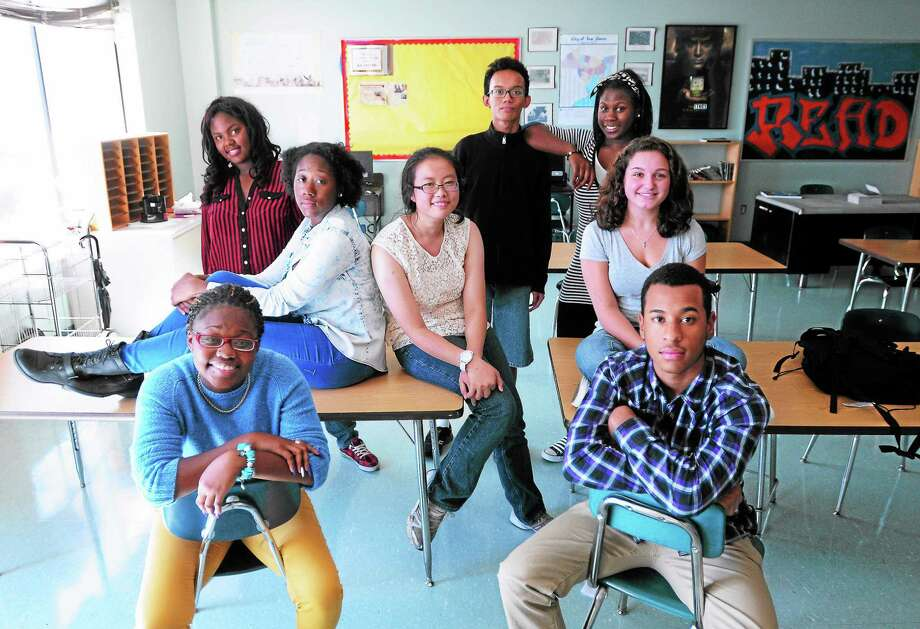 (Arnold Gold — New Haven Register)  Clockwise from bottom left, journalism class members Shainah Andrews, 16, Asiayana McCain, 14, Erica Carr, 16, Amy Zheng, 16, Alif Albiruni, 16,Tawaka Henderson, 18, Marisa Misbach, 16, and Angel Guzman, 16, are photographed at the High School in the Community in New Haven on 9/19/2013. Photo: Journal Register Co.