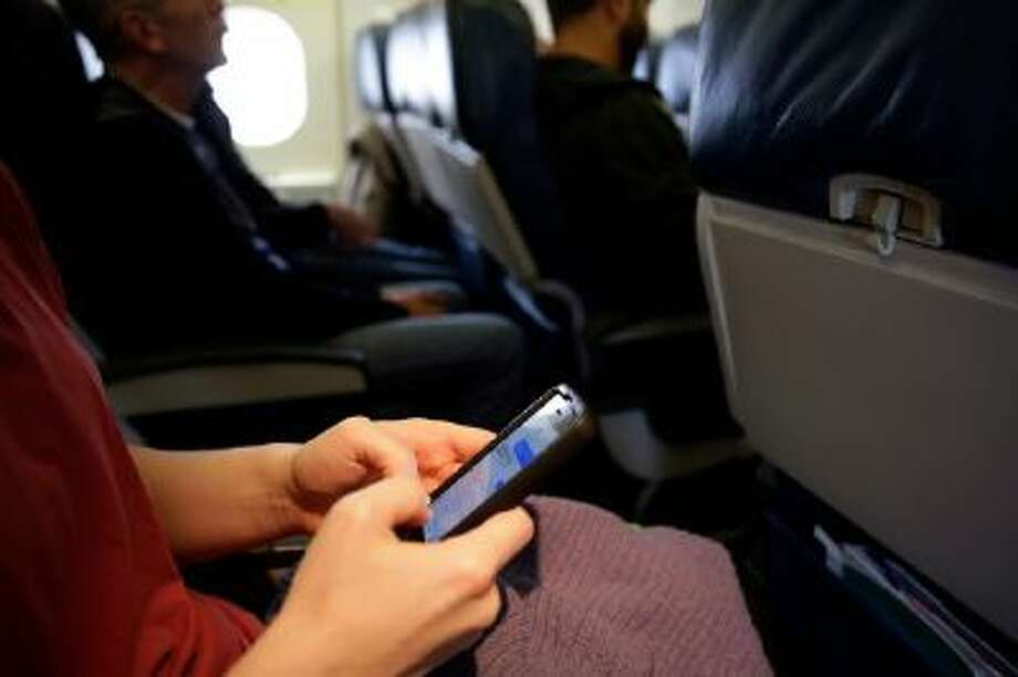 In this Oct. 31, 2013 photo, a passenger checks her cell phone before a flight in Boston.