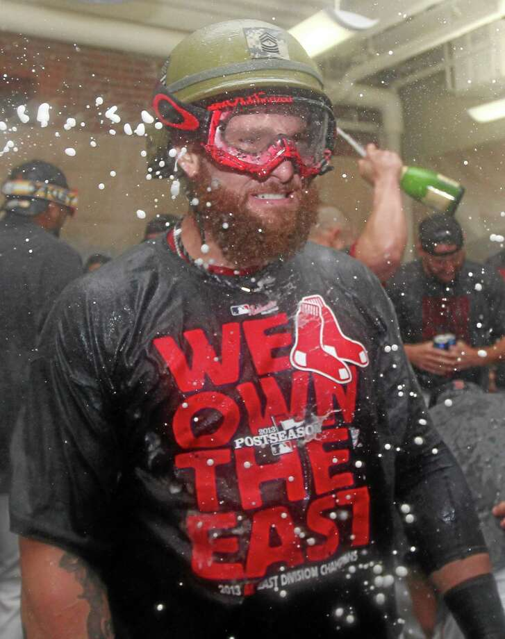 As sparkling wine is sprayed around the clubhouse, Boston Red Sox left fielder Jonny Gomes grits his teeth as he celebrates with a crash helmet on after the Red Sox clinched the AL East title with a 6-3 win over the Toronto Blue Jays Friday at Fenway Park. Photo: Charles Krupa — The Associated Press   / AP