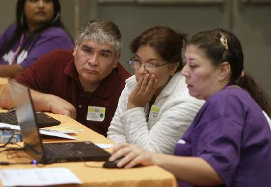 Carlos Barajas, left, and his wife, Martha, center, look over their health insurance plan options with volunteer Elizabeth Lira, at a health fair in Sacramento, Calif. in November 2013.