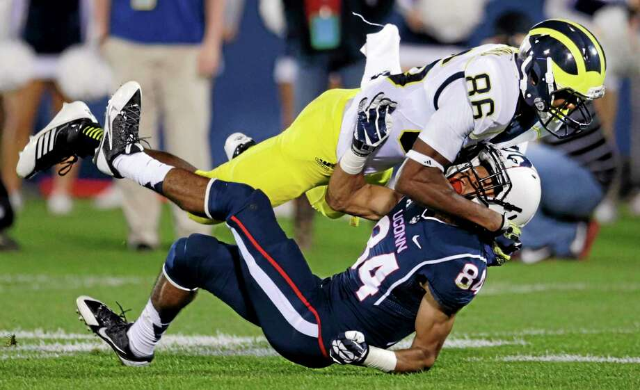 Michigan's Jehu Chesson levels UConn's Brian Lemelle on a punt return during the second quarter Saturday at Rentschler Field. Photo: Charles Krupa — The Associated Press   / AP