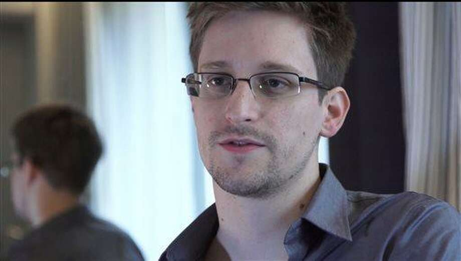 This Sunday, June 9, 2013 file photo provided by The Guardian Newspaper in London shows Edward Snowden, in Hong Kong. Russian state news agency said Wednesday, July 24, 2013 that US leaker Edward Snowden has been granted a document that allows him to leave the transit zone of a Moscow airport and enter Russia.  Snowden has applied for temporary asylum in Rusia last week after his attempts to leave the airport were thwarted. The United States wants him sent home to face prosecution for espionage.  (AP Photo/The Guardian, Glenn Greenwald and Laura Poitras, File) Photo: AP / The Guardian