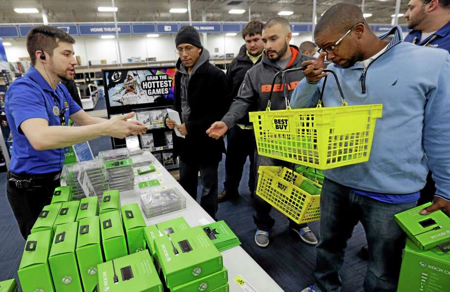 Nikolai Vacca, left, explains Xbox One accessories to customers at a Best Buy store on Friday, Nov. 22, 2013., in Evanston, Ill.  Microsoft is billing the Xbox One, which includes an updated Kinect motion sensor, as an all-in-one entertainment system rather than just a gaming console. Photo: Nam Y. Huh — The Associated Press / AP