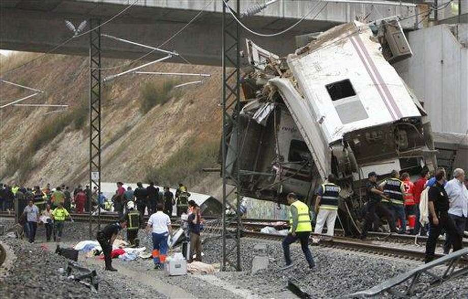Emergency personnel respond to the scene of a train derailment in Santiago de Compostela, Spain, on Wednesday, July 24, 2013. A train derailed in northwestern Spain on Wednesday night, toppling passenger cars on their sides and leaving at least one torn open as smoke rose into the air. Dozens were feared dead, with possibly even more injured. (AP Photo/ El correo Gallego/Antonio Hernandez) Photo: AP / AP