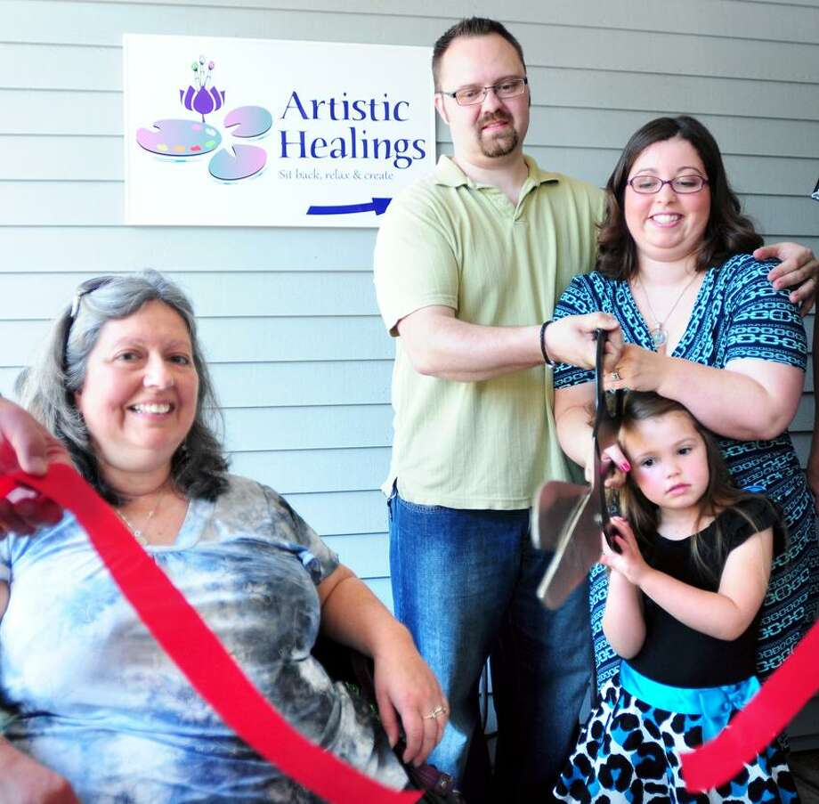 Stephanie O'Sullivan (far right), owner of Artistic Healings, cuts a ribbon with her family in front of the store in Guilford on 5/21/2013.  Left to right are Stephanie's mother, Kim Hodge, husband, Dan, and daughter, Emily 4.Photo by Arnold Gold/New Haven Register   AG0499B