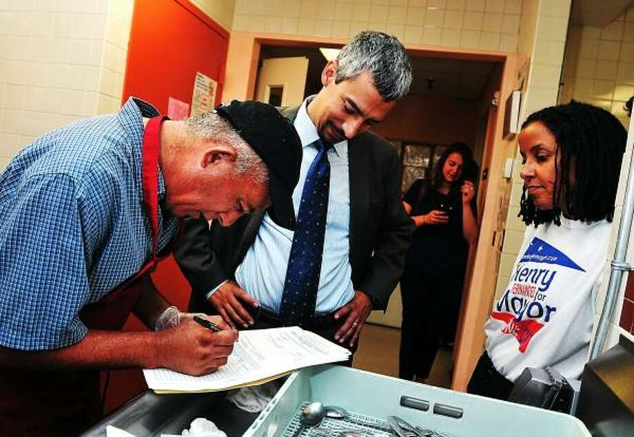 """Mayoral candidate Henry Fernandez gets a signature from Israel Vazquez, part of the kitchen crew at Casa Otonal, as Fernandez was collecting signatures to get on the primary ballot. On the right is Fernandez' wife, Kica Matos. Peter Casolino/New Haven Register  <a href=""""mailto:pcasolino@newhavenregister.com"""">pcasolino@newhavenregister.com</a>"""