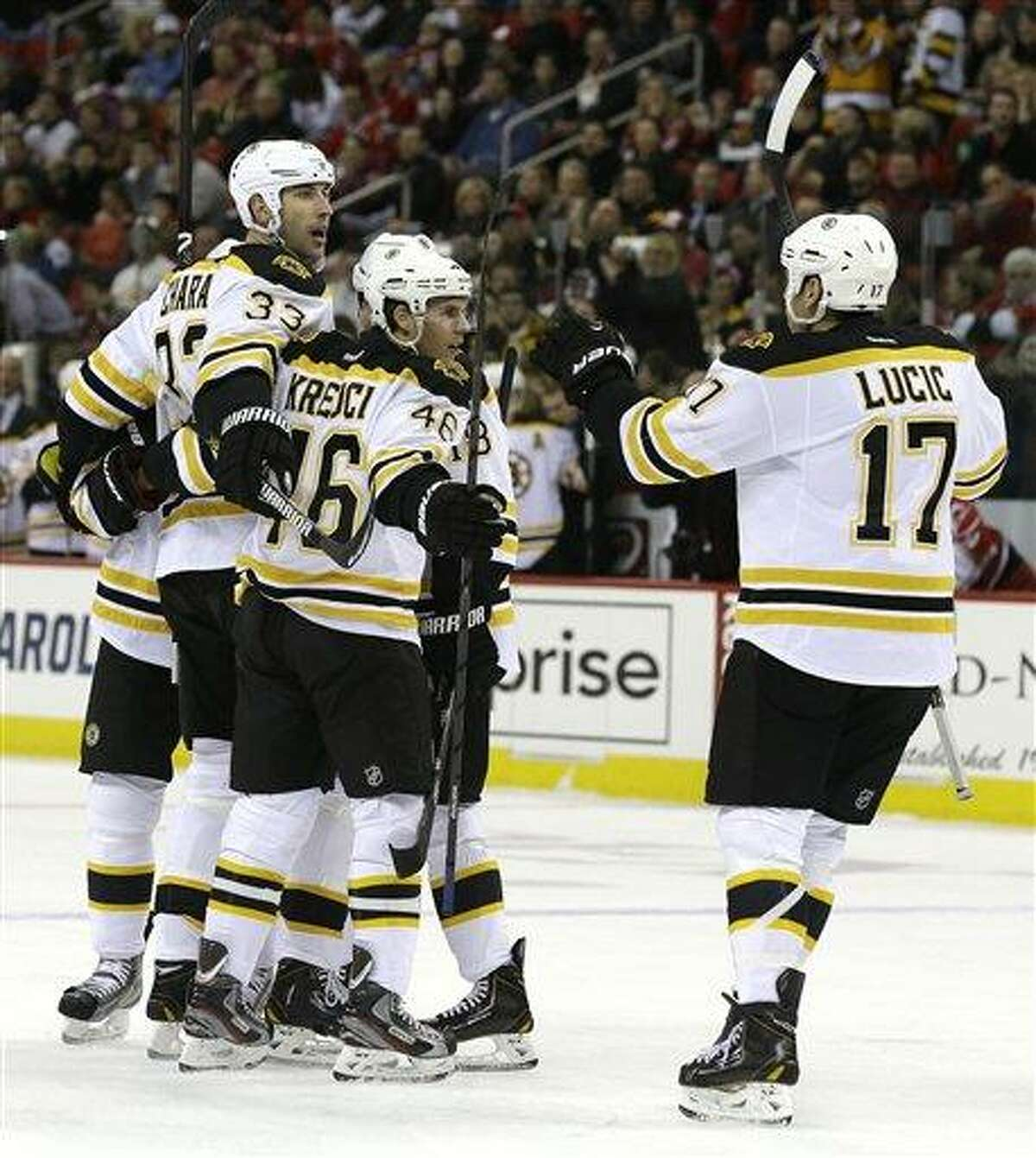 Boston Bruins' Zdeno Chara (33), of Slovakia, is congratulated by David Krejci (46), of the Czech Republic, and Milan Lucic (17) after Chara's goal against the Carolina Hurricanes during the first period of an NHL hockey game in Raleigh, N.C., Monday, Jan. 28, 2013. Boston won 5-3. (AP Photo/Gerry Broome)