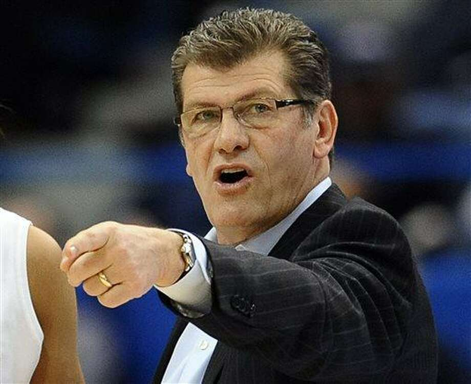 FILE - In this March 11, 2013, file photo, Connecticut head coach Geno Auriemma talks with players during the first half of an NCAA college basketball game against Syracuse in the semifinals of the Big East Conference tournament in Hartford, Conn.  Auriemma has signed a new $10.86 million contract, a deal designed to keep him at the school through the 2017-18 season, UConn announced Wednesday, March 27, 2013. (AP Photo/Jessica Hill, File) Photo: AP / FR125654 AP