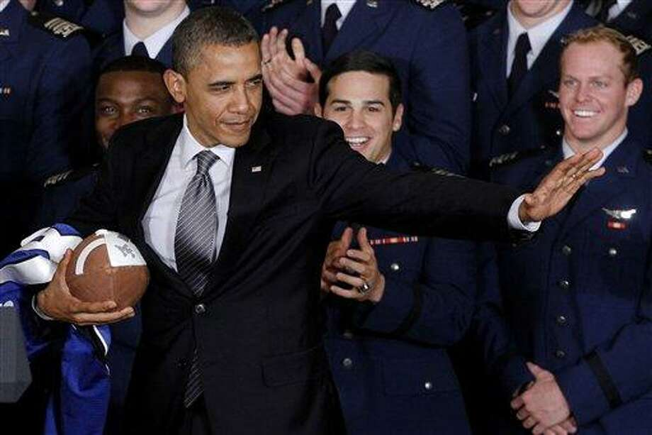President Obama strikes the Heisman pose after he awarded the Commander-in-Chief Trophy to the Air Force Academy football team at the White House in Washington. ?I'm a big football fan, but I have to tell you, if I had a son, I'd have to think long and hard before I let him play football,? President Barack Obama tells The New Republic. In an interview in the magazine?s Feb. 11 issue, Obama says he worries more about college players than he does about those in the NFL. AP Photo/Charles Dharapak Photo: AP / AP