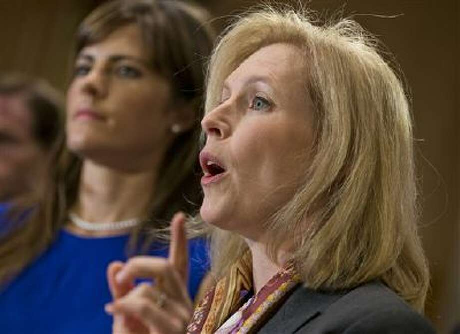 Sen. Kirsten Gillibrand, D-N.Y., joined by Sarah Plummer, left, a Marine Corps veteran and victim of sexual assault, speaks Tuesday during a news conference on Washington. They are joined by supporters of her proposal to let military prosecutors rather than commanders make decisions on whether to prosecute sexual assaults in the armed forces. Photo: AP / AP