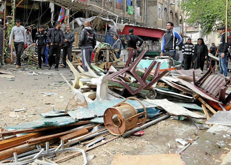 Iraqis inspect the aftermath of a late-night bombing at a cafe in Bayaa neighborhood, southwestern Baghdad, Iraq, Thursday, Nov. 21, 2013. Officials in Iraq say scores have been killed in a wave of bombings on Wednesday, Nov. 20, 2013 mainly in Shiite commercial areas in and near the capital. (AP Photo/Karim Kadim) Photo: AP / AP
