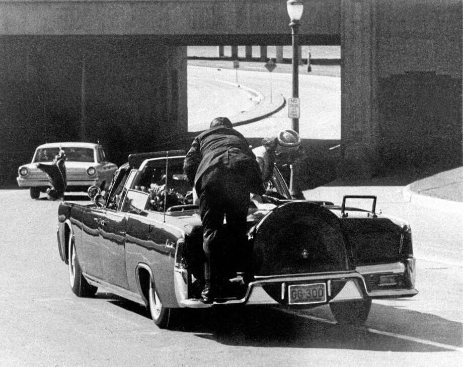 """FILE — In this Friday, Nov. 22, 1963, file photo, President John F. Kennedy slumps down in the back seat of the presidential limousine as it speeds along Elm Street toward the Stemmons Freeway overpass in Dallas after being fatally shot. First lady Jacqueline Kennedy climbs onto the trunk as Secret Service agent Clint Hill pushes her back to her seat. """"She's going to go flying off the back of the car,"""" Hill thought as he tried to secure the first lady. (AP Photo/James W. """"Ike"""" Altgens) Photo: AP / AP"""
