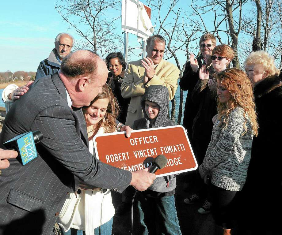 The bridge that connects West Haven and New Haven at Kimberly Avenue was named in honor of late New Haven police Officer Robert Fumiatti Thursday. State Rep. Stephen Dargan gives a small version of the sign to Fumiatti's widow Stacey and two of the couple's children, Vincent, 9, and Madelyn, second from right. Also there were State Rep. Louis Esposito, New Haven Mayor-elect Toni Harp, West Haven Mayor John M. Picard, Fumiatti's brother, Michael, nephew, Lucas, and mother, Marguerite. Photo: Mara Lavitt — New Haven Register       / Mara Lavitt