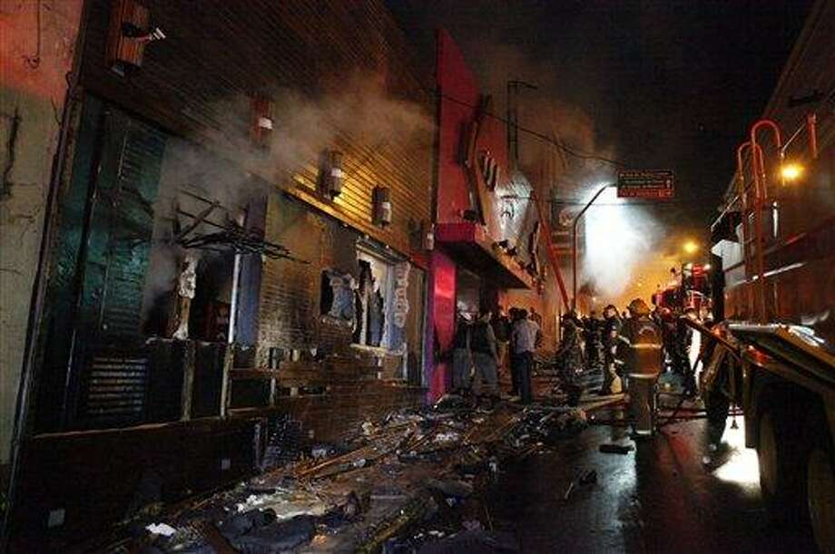 Firefighters work to douse a fire at the Kiss Club in Santa Maria city, Rio Grande do Sul state, Brazil, Sunday, Jan. 27, 2013. Firefighters say that the death toll from a fire that swept through a crowded nightclub in southern Brazil. (AP) Photo: ASSOCIATED PRESS / AP2013