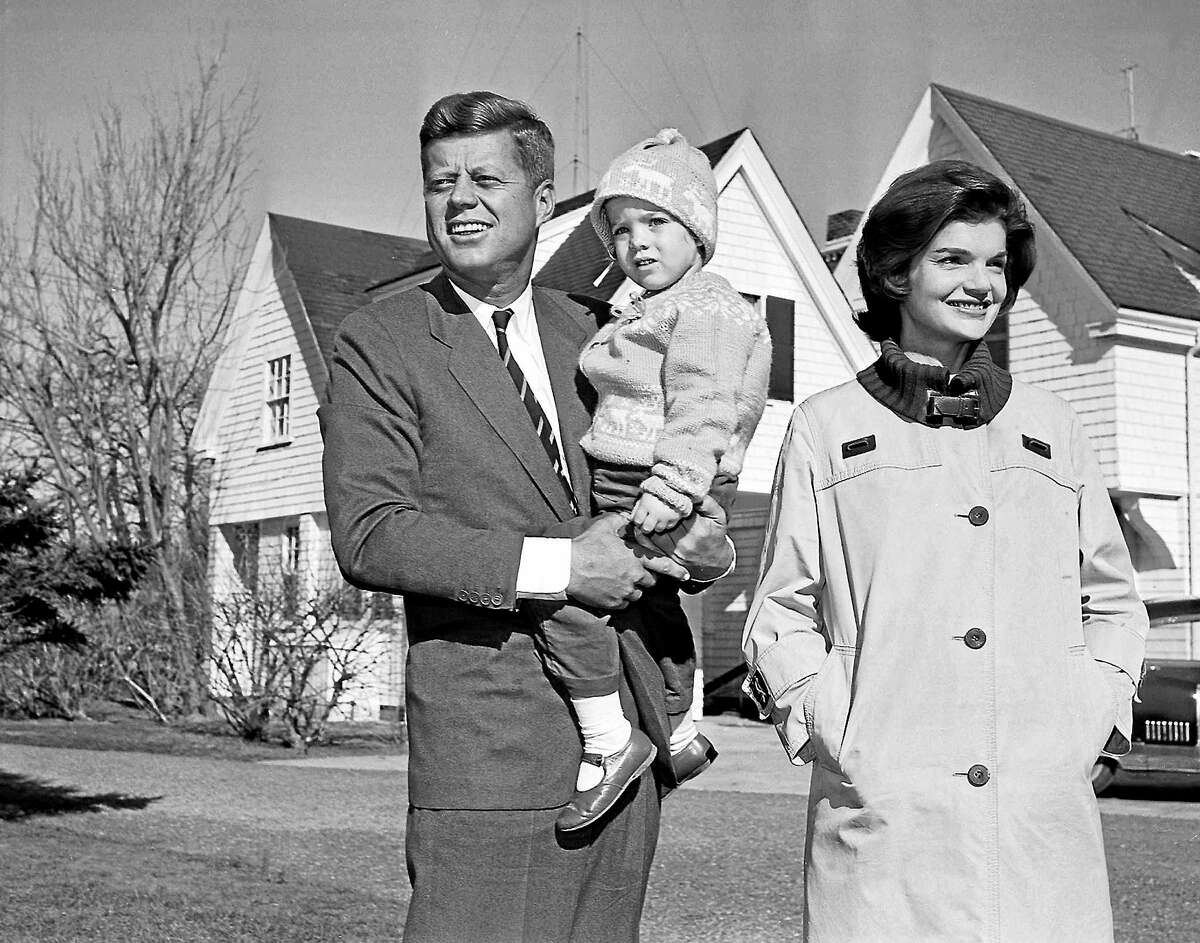 Sen. John F. Kennedy, Democrat presidential nominee, is shown with his wife, Jacqueline, as he holds their daughter, Caroline, outside their home in Hyannis Port, Mass. on Nov. 8, 1960. (AP Photo)