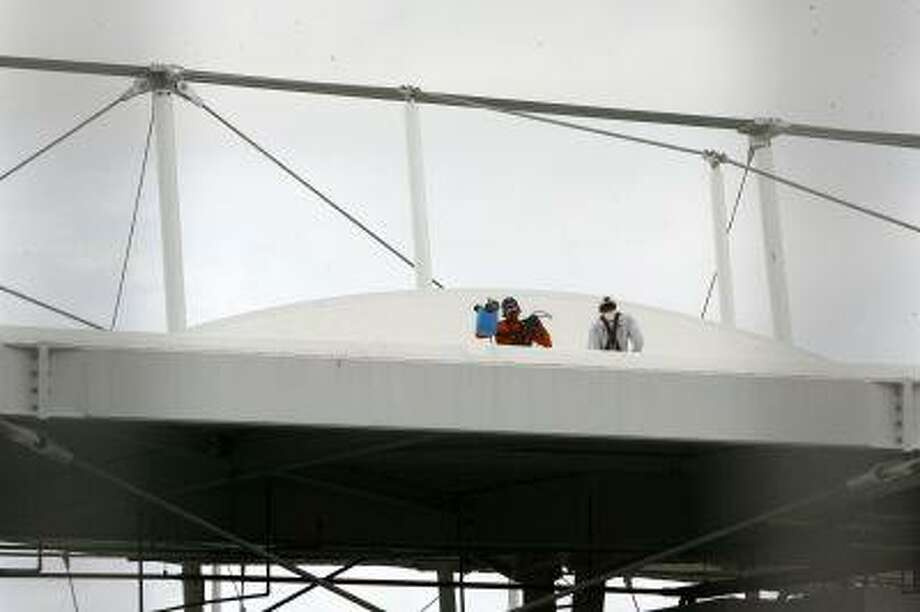 Men work on the roof of the Fonte Nova stadium after heavy rain in preparation for the 2013 Confederations Cup, in Salvador May 27, 2013. Heavy rains in the northeastern city of Salvador tore through the roof of a newly constructed stadium that will host games during the upcoming Confederations Cup, a warm-up before Brazil hosts the World Cup of soccer next year. Rains, local authorities said, ripped a large swath out of one of 36 panels of textile stretched above the seating in the arena. Televised images of the facility showed a large triangular tear in the covering that dwarfed workers gathered around the rim of the hole to inspect it. Though local officials say the roof will be repaired before Confederations games begin June 15, the damage underscores concerns about preparedness in Brazil as it gears up to host the World Cup, in twelve Brazilian cities in 2014, and the 2016 Olympics in Rio de Janeiro. Photo: REUTERS / X01489