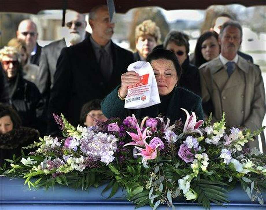 "Linda Phiel places a ""Whopper Jr."" sandwich from Burger King on the casket to be buried with her father David Kime, Jr. at Prospect Hill Cemetery in York, Pa. on Saturday, Jan. 26, 2013.  Phiel and other mourners went through the drive-through at Burger King and each got the hamburger to honor Kime, Jr. who loved fast food.  AP Photo/York Daily Record, Jason Plotkin Photo: AP / York Daily Record"