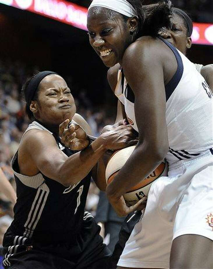San Antonio Silver Stars' Jia Perkins, left, scramble with Connecticut Sun's Tina Charles for possession of the ball during the first half of a WNBA basketball game in Uncasville, Conn., Sunday, July 14, 2013. (AP Photo/Jessica Hill) Photo: AP / FR125654 AP