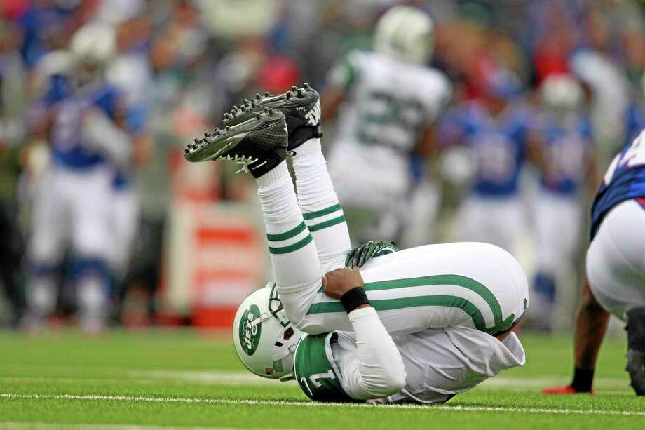 New York Jets quarterback Geno Smith gets knocked over by a Buffalo Bill during the first half of Sunday's game in Orchard Park, N.Y. Photo: Harry Scull Jr. — The Associated Press   / The Buffalo News