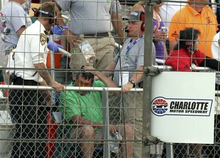In this photo provided by Fernando Echeverria, security personnel assist a fan injured by a broken television camera cable during the NASCAR Sprint Cup series Coca-Cola 600 auto race at Charlotte Motor Speedway in Concord, N.C., Sunday, May 26, 2013. (AP Photo/Fernando Echeverria) Photo: AP / Fernando Echeverria