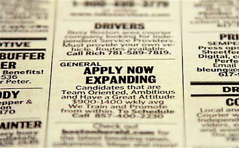 In this Tuesday, Dec. 11, 2012 photo taken in Walpole, Mass., an advertisement in the classified section of the Boston Herald newspaper calls attention to possible employment opportunities.  The number of Americans seeking unemployment benefits fell sharply for a fourth straight week, a sign that the job market may be improving. The Labor Department said Thursday, Dec. 13, 2012, that weekly applications for unemployment benefits fell 29,000 last week to a seasonally adjusted 343,000, the lowest in two months. It is the second-lowest total this year. (AP Photo/Steven Senne) Photo: ASSOCIATED PRESS / The Associated Press2012
