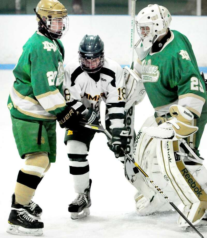 Matthew Barnett (center) of Hamden is sandwiched between Kyle Lynch (left) and goalie Luc Amatruda (right) of Notre Dame of West Haven in the first period on 1/26/2013.Photo by Arnold Gold/New Haven Register