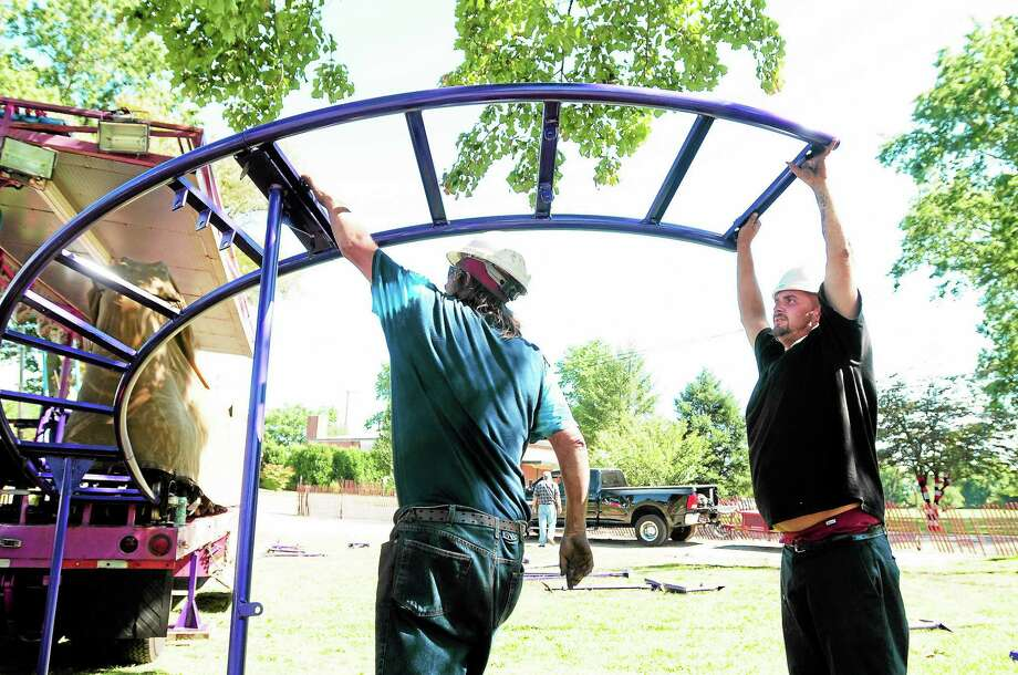 (Arnold Gold — New Haven Register)  John Ral (left) and Shaun Ball of Marenna Amusements put together the track for the Dragon Wagon ride next to the High Plains Community Center in Orange for the Orange Country Fair on 9/19/2013.  The fair takes place on 9/21-9/22. Photo: Journal Register Co.