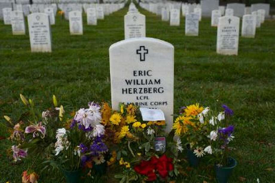 Flowers adorn the gravesite of U.S. Marine, Lance Cpl. Eric W. Herzberg in Arlington National Cemetery. Flowers may soon be the only decoration families can leave at gravesites there. Photo: The Washington Post/Getty Images / 2013 The Washington Post