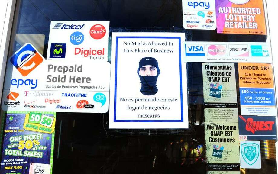 A sign prohibiting wearing face masks is posted on the front door of the Grand Ave. Deli at 271 Grand Ave. in New Haven where a robbery occurred on 1/24/2013.  The signs on local businesses have been distributed by the New Haven Police Department.Photo by Arnold Gold/New Haven Register   AG0481E