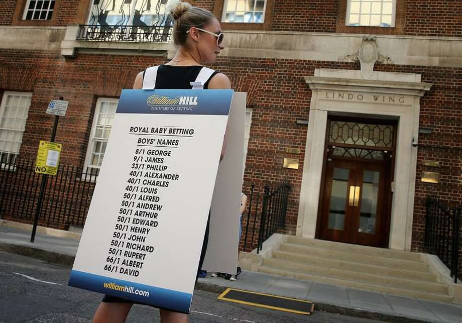 A girl from a Betting Company wears a board highlighting the latest odds on babies names outside the Lindo wing of St Mary's Hospital as the UK prepares for the birth of the first child of The Duke and Duchess of Cambridge on July 16, 2013 in London, England.  (Photo by Chris Jackson/Getty Images) Photo: Getty Images / 2013 Getty Images