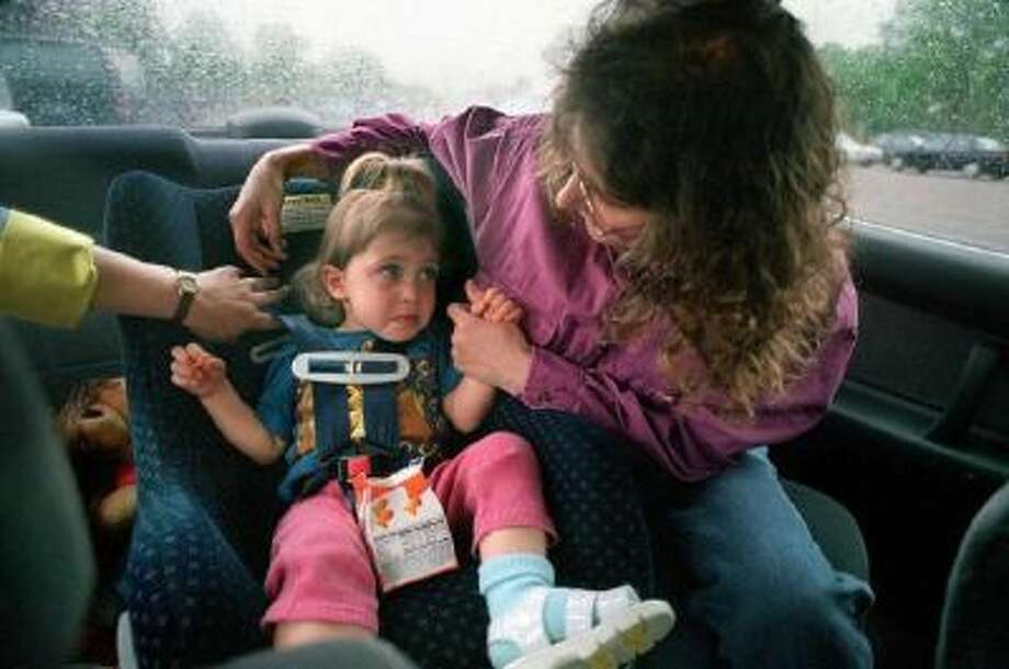 Stacy Segal checks the belts on the car seat holding her daughter, Jamie Hanson, 2. Segal is a child passenger safety specialist who helps parents insure that their child car seats are installed properly.
