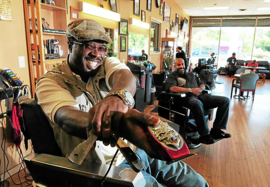 (Photo by Peter Hvizdak — Register)Troy Turner, co-owner of BladeZ Barbershop in West Haven shows of one of his many collectible razors, left, with Brian MacCalla, co-owner. Wednesday September 18, 2013. Photo: New Haven Register / ©Peter Hvizdak /  New Haven Register