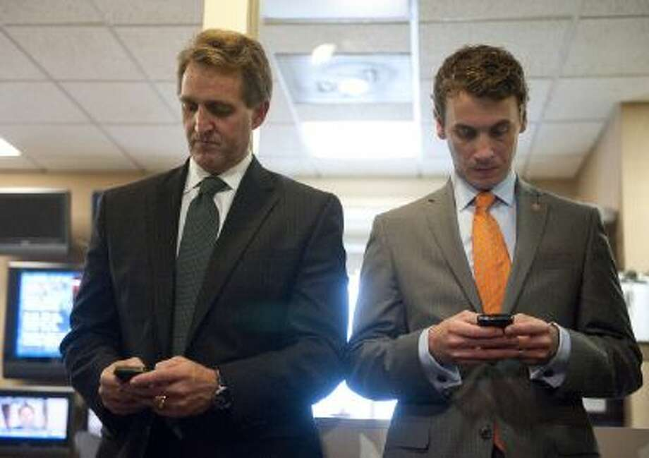 Rep. Jeff Flake and Rep. Ben Quayle, both Republicans from Arizona, use their smartphones. There's a popular app for members of Congress to keep track of votes. Photo: Roll Call/Getty Images / © CQ Roll Call