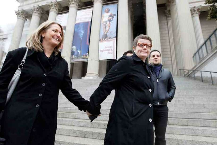 Sandy Stier, left, and Kris Perry of Berkeley, Calif., stand outside the National Archives in Washington, Monday, March 25, 2013, before going inside to view the U.S. Constitution, a day before their same-sex marriage case is argued before the Supreme Court. (AP Photo/Jose Luis Magana) Photo: ASSOCIATED PRESS / THE ASSOCIATED PRESS2013