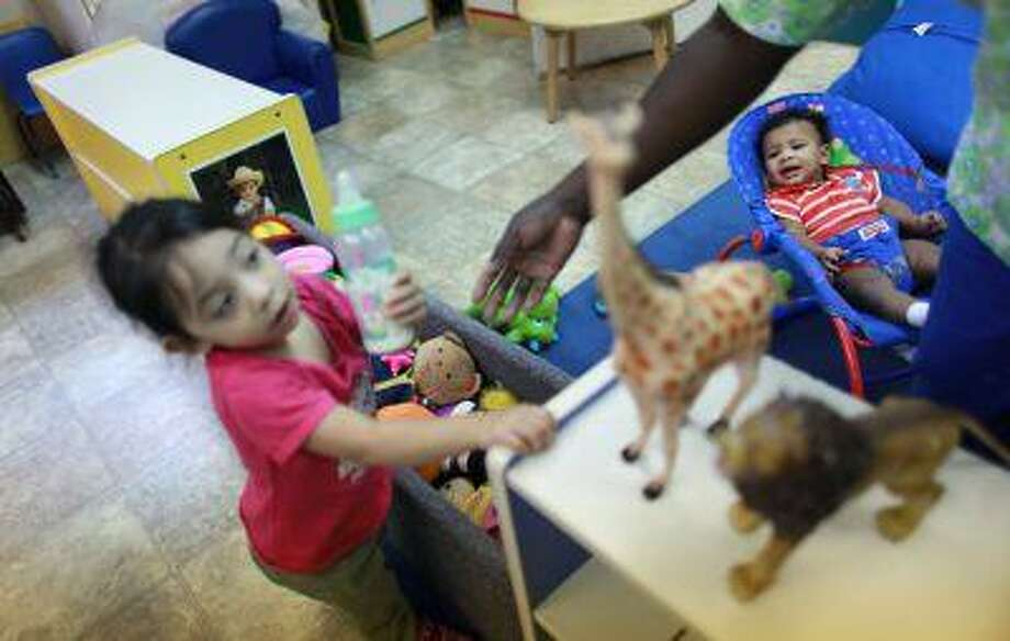Daycare teacher Yvette Santos takes care of the kids, including 8-month-old Johan Leon, right, at the Westcop Whitney Young Head Start daycare facility in Yonkers, N.Y. Photo: THE WASHINGTON POST / Yana Paskova