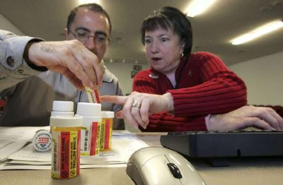 Volunteer Rebecca Cox, right, helps a man log prescription drug information as he registers his parents for the new Medicare drug prescription program during an enrollment event in December 2005 in Pleasanton, Calif.