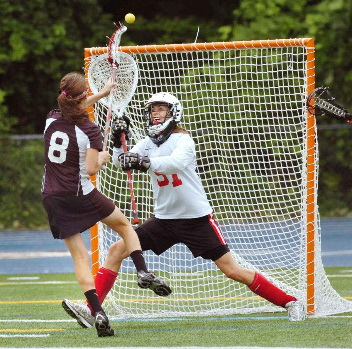 Olivia Hompe, #8, of New Canaan High School, left, scores the lst goal of the game against Greenwich High School goalie, Kaitlin Bedford, # 51, during the 2010 Girls Lacrosse State Division 1 Finals at Bunnell High School, Stratford, Saturday afternoon, June 12, 2010. New Canaan won the championship over GHS, 10-9.