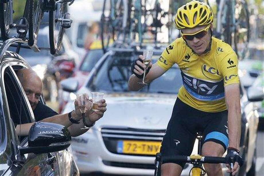 Christopher Froome of Britain, wearing the overall leader's yellow jersey, toasts with Sky Procycling team manager David Brailsford of Britain, left, during the 21st and last stage of the 100th edition of the Tour de France cycling race over 133.5 kilometers (83.4 miles) with start in Versailles and finish in Paris, France, Sunday July 21 2013. (AP Photo/Laurent Cipriani) Photo: AP / AP