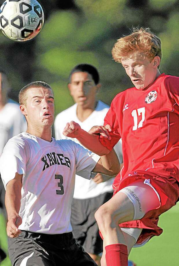 Xavier's Brendan Charton battles Cheshire's Justin Kunz for possession in the second half of Tuesday's game at TD Bank Oakwood Soccer Park in Portland. The game ended in a 0-0 tie. Photo: Brittany Hill — Middletown Press   / TheMiddletownPress