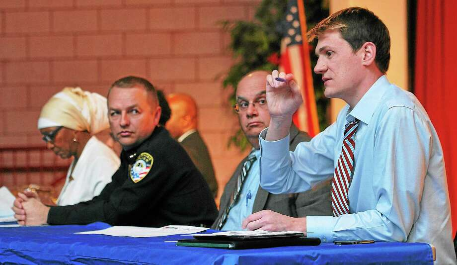 Ken Barone, right, a project staff member at Central Connecticut State University, speaks during a town hall meeting  on racial profiling Wednesday. Also pictured are, front to back, New Haven police Assistant Chief Archie Generoso, Cheshire Police Chief Neil Dryfe and Emma Jones of New Haven. Photo: Peter Casolino — New Haven Register