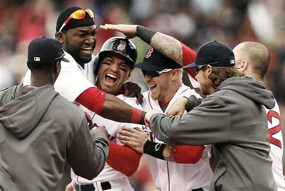 Boston Red Sox's Jacoby Ellsbury, third from left, is mobbed by David Ortiz, second from left, and other teammates after his walkoff two-run double during the ninth inning of a 6-5 win over the Cleveland Indians in a baseball game at Fenway Park in Boston, Sunday, May 26, 2013. (AP Photo/Winslow Townson) Photo: AP / FR170221 AP
