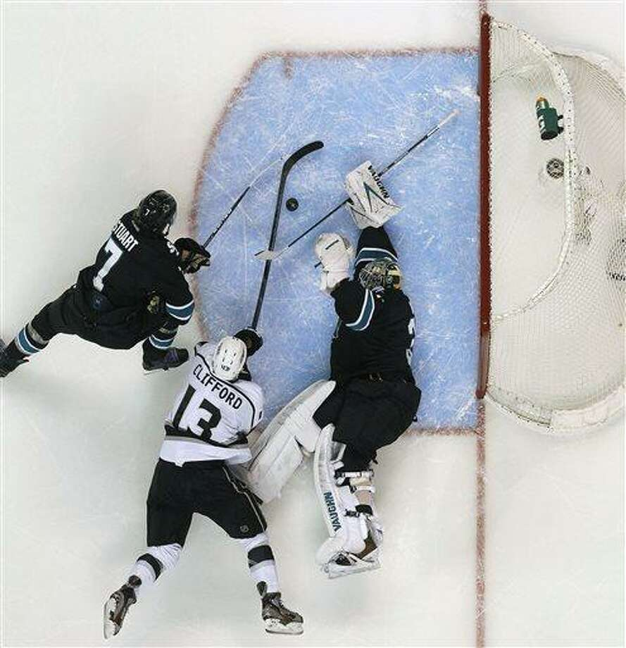 San Jose Sharks goalie Antti Niemi (31), of Finland, blocks a goal attempt by Los Angeles Kings left wing Kyle Clifford (13) as Sharks defenseman Brad Stuart (7) defends during the second period in Game 6 of their second-round NHL hockey Stanley Cup playoff series in San Jose, Calif., Sunday, May 26, 2013. (AP Photo/Tony Avelar) Photo: AP / FR155217 AP